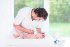 Potomstwa ojcują zmieniać pieluszkę przy jego małym dziecko synem fotografia stock