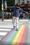 Potomstwa ostrożny dziecko krzyżuje ulicę z zabawą, miasta tło zdjęcia stock