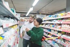 Potomstwa, piękna para nabywcy wybierają plastikowych naczynia w supermarkecie Wybór towary w sklepie zdjęcie royalty free