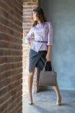 Potomstwa, piękna dziewczyna z torby pozycją przy okno Obraz Stock