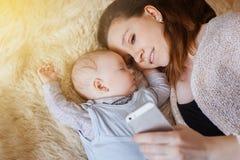 Potomstwa, piękna matka bierze selfie ty i dziecko na twój smartphone sunlight zdjęcia stock