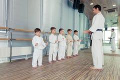 Potomstwa, piękni, pomyślni wielo- etyczni dzieciaki w karate positi, Zdjęcia Stock
