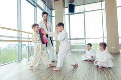 Potomstwa, piękni, pomyślni wielo- etyczni dzieciaki w karate pozyci, Zdjęcie Royalty Free