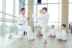 Potomstwa, piękni, pomyślni wielo- etyczni dzieciaki w karate pozyci, Obrazy Royalty Free