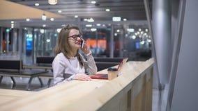 Potomstwa, pi?kna dziewczyna opowiada na telefon pozyci przy sto?em z laptopem przy lotniskiem i fili?anka kawy, zbiory wideo