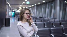 Potomstwa, pi?kna dziewczyna opowiada na telefonie w pustym lotniskowym terminal zdjęcie wideo