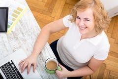 Potomstwa plus wielkościowa kobieta pracuje na laptopie zdjęcia stock