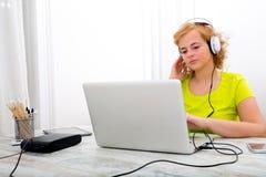 Potomstwa plus wielkościowa kobieta słucha audio podczas gdy pracujący na lapt zdjęcia stock