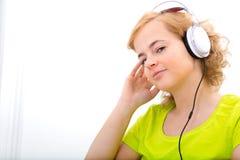 Potomstwa plus wielkościowa kobieta słucha audio podczas gdy pracujący na lapt obraz royalty free
