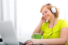Potomstwa plus wielkościowa kobieta słucha audio podczas gdy pracujący na lapt zdjęcie stock