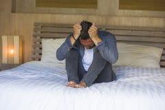 Potomstwa przytłaczający i deprymujący mężczyzny obsiadanie na łóżku martwiącym się i udaremniającym cierpiący depresja kryzys ci obrazy royalty free
