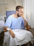 Potomstwa ranili mężczyzna siedzi samotnie w bólu martwiącym się dla jego stanu zdrowia w sala szpitalnej Obrazy Royalty Free