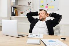 Potomstwa relaksowali biznesmena z laptopem w nowożytnym białym biurze zdjęcia stock