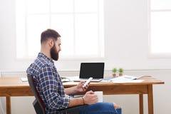 Potomstwa relaksowali biznesmena z laptopem w nowożytnym białym biurze Obraz Royalty Free