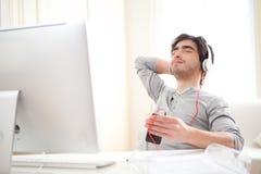 Potomstwa relaksujący obsługują listenning muzykę przy biurem fotografia stock