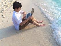 Potomstwa relaksujący obsługują z laptopu obsiadaniem na piaskowatej plaży z miękkimi falami Internet rzeczy pojęcie fotografia royalty free