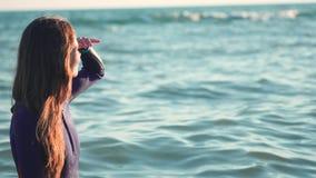 Potomstwa schudnięcia kipieli dziewczyna patrzeje zmierzch Pławiki na kolor żółty desce w otwartym morzu, czekaniach dla fala i s zbiory wideo