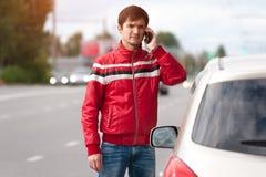 Potomstwa spęczenia mężczyzna dzwoni samochodowa pomoc na drodze Fotografia Royalty Free