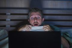 Potomstwa straszący i stresujący się mężczyzna w łóżkowym dopatrywanie interneta horrorze nocnym z laptopem wewnątrz lub sypialni obraz stock