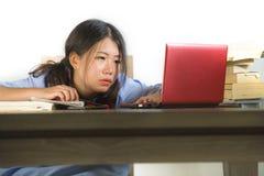 Potomstwa stresujący się i udaremniająca Azjatycka Koreańska studencka dziewczyna pracuje mocno z laptopem i książkami wypiętrzaj obrazy royalty free