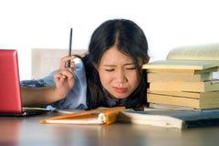 Potomstwa stresujący się mocno z, udaremniający Azjatyckiego Chińskiego nastolatka studencki pracujący i wypiętrzają na biurku pr zdjęcie royalty free