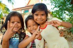 Potomstwa, szczęśliwe Kambodżańskie dziewczyny na zewnątrz społeczność budynków zdjęcie stock
