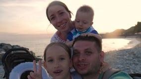 Potomstwa, szczęśliwy rodzinny magnetofonowy wideo, bierze selfie blisko morza przy zmierzchem zbiory wideo