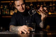 Potomstwa tatuowali barmanu stawia kostka lodu w koktajlu szkło fotografia royalty free