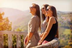 Potomstwa trzy dziewczyny uśmiecha się zabawę outdoors i ma Zdjęcia Royalty Free