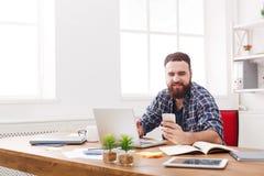 Potomstwa uśmiechali się biznesmena w biurowym używa telefonie komórkowym laptopem Obraz Stock
