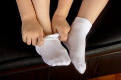 Potomstwa Uczą kogoś dziewczyna ucznia Jest ubranym Białe skarpety zdjęcie stock