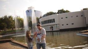 Potomstwa wychowywają z córką przy fontanną przy zmierzchem zbiory