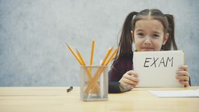 Potomstwa, z włosami dziewczyny obsiadanie przy stołem Podczas ten inskrypcji w rękach egzamin Żałosnego spojrzenie zbiory wideo