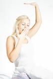 Potomstwa zaświecają włosianego kobieta modela streching i ziewa w łóżku, fotografia stock