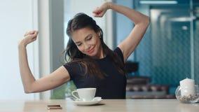 Potomstwa zanudzali brunetki ziewanie, rozciąganie i pić kawa w kawiarni obrazy royalty free