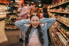Potomstwo córka w sklepie spożywczym i rodzice Dziewczyna krzyczy i płacze Utrzymuje ucho zamyka Ona rodzice dyskutować i obraz royalty free