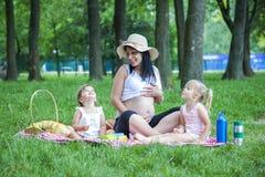 Potomstwo ciężarna matka z dwa dziewczynami na pykniczny bawić się obraz stock