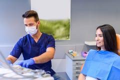 Potomstwo dentysta taktuje żeńskiego pacjenta w stomatologicznym studiu fotografia stock