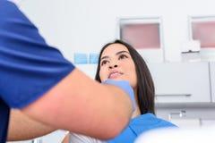 Potomstwo dentysta taktuje żeńskiego pacjenta w stomatologicznym studiu obraz stock