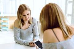 Potomstwo dosyć caucasian dziewczyna patrzeje w telefonie zdjęcie royalty free