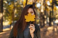 Potomstwo dosyć elegancka kobieta z niebieskimi oczami w modnym zielonym żakiecie, trzyma żółtego jesień liść blisko twarzy podcz zdjęcia stock