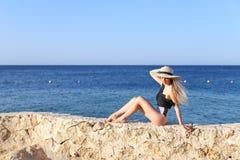 Potomstwo dosyć gorąca seksowna kobieta relaksuje w swimsuit na kamieniach z błękitnym morzem i niebie na tle Wakacje poj?cie obrazy royalty free