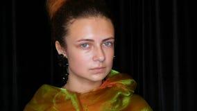 Potomstwo dosyć miedzianowłosa nastoletnia dziewczyna w czarnych kolczykach i szalika zielone pozy bez makeup w wzorcowym fotogra zdjęcie wideo