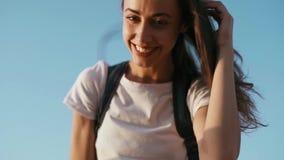 Potomstwo dosyć radosna kobieta w białej koszulce jest trwanie na niebieskiego nieba tle, prostuje włosy ręcznie, i patrzejący zdjęcie wideo