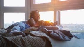 Potomstwo dosyć szczęśliwa kobieta kłaść w dół w łóżku z telefonu komórkowego i Maine Coon kotem bierze selfy okno podczas zmierz zdjęcie wideo