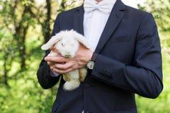 Potomstwo fornal trzyma białego ślicznego królika w jego ręce na zielonym tle, lato Obrazy Royalty Free