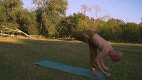 Potomstwo Garbnikujący facet Wykonuje joga Asanas W ranku na haliźnie w miasto parku zdjęcie wideo