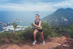 Potomstwo kobiety śladu napad garbnikuję działający up kroki rzeźbił w zbocze z górami, morzem, wyspami i chmurnym niebem, zdjęcia stock