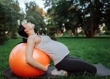 Potomstwo koncentrująca kobieta w ciąży siedzi na kolanach na joga szturmanie w parku Opiera pomarańczowa sprawności fizycznej pi zdjęcia stock