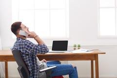 Potomstwo koncentrujący biznesmen mobilną rozmowę w nowożytnym białym biurze Zdjęcia Royalty Free